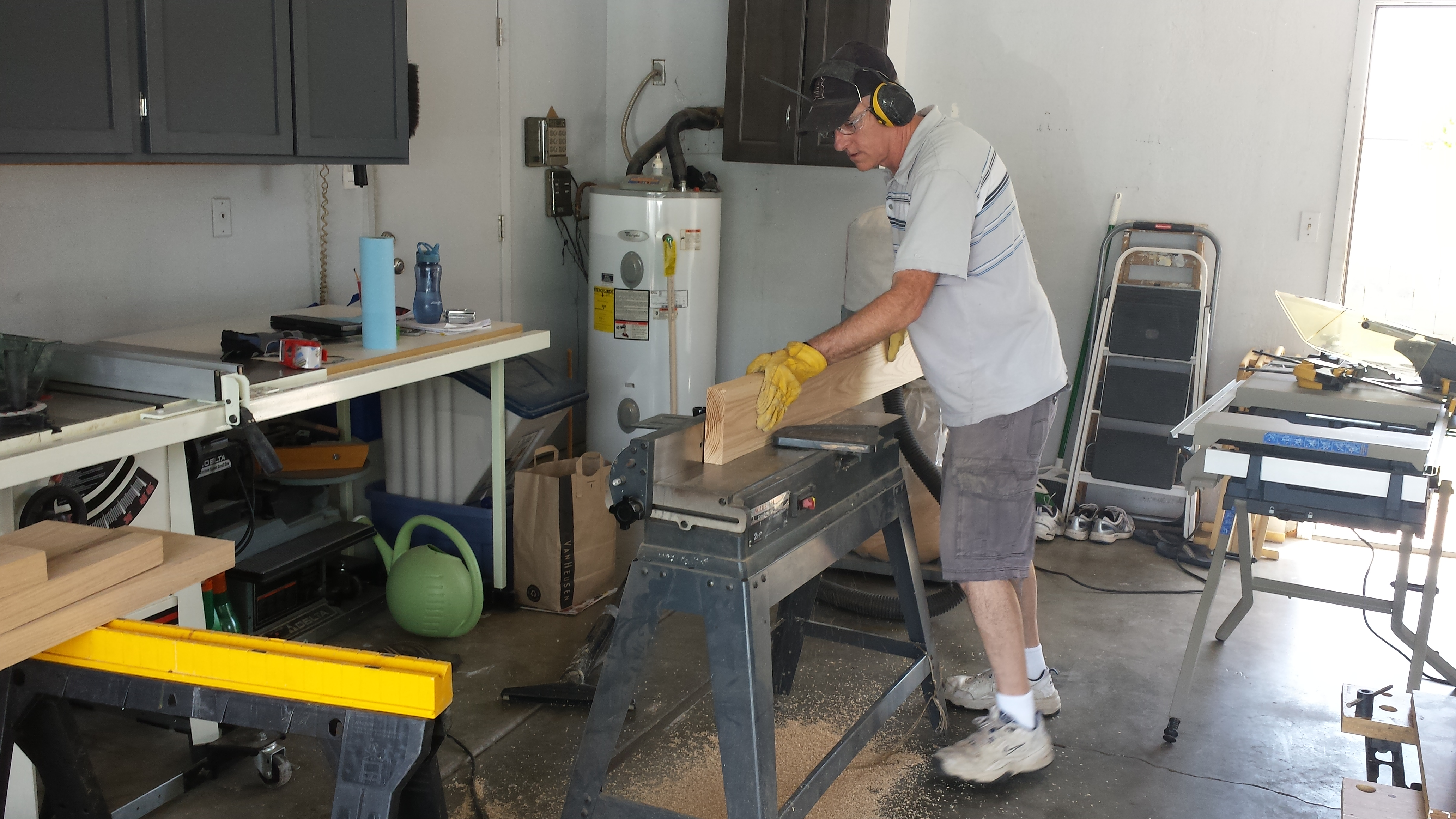 My dad using the jointer to square up the edges and make a nice flat surface for the legs of the furniture.